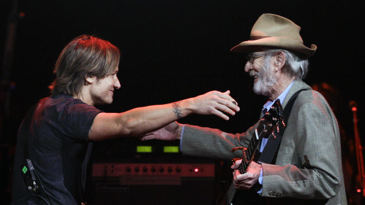 Keith Urban, left, hugs Country Music Hall of Fame member Don Williams as Williams takes the stage to perform during the All for the Hall concert on Tuesday, April 10, 2012, in Nashville, Tenn. The concert is a benefit for the Country Music Hall of Fame and Museum. (AP Photo/Mark Humphrey)