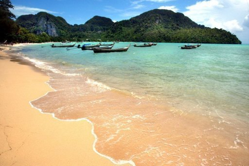 Boats moored off a beach in southern Thailand on July 24, 2002. A 22-year-old British tourist was shot dead as he danced at a New Year party on one of Thailand's most famous islands after a fight between rival Thai gangs erupted on the beach, police said on Tuesday.