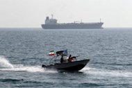 Iranian Revolutionary Guards drive a speedboat in front of an oil tanker near the port of Bandar Abbas in July 2012. South Korean oil refiners are in talks with Iran to resume oil imports, officials said Thursday, potentially by using Iranian tankers as a way to circumvent European Union sanctions