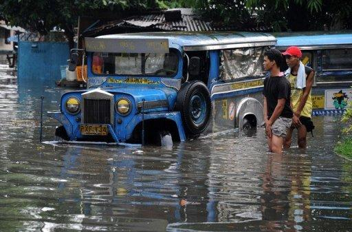 File picture shows people wading through a flooded street in Manila  in May after heavy rain
