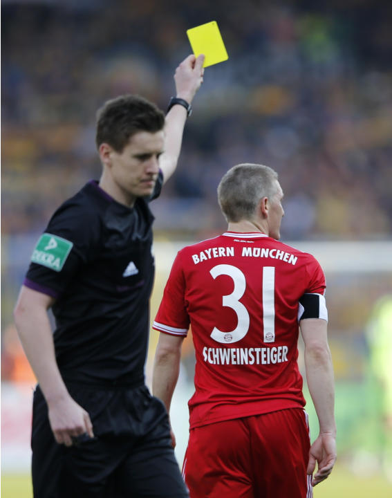 Referee shows yellow card to Bayern Munich's Schweinsteiger during Bundesliga soccer match against Eintracht Braunschweig in Berlin