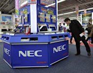 A customer inspects laptops from Japanese electronics maker NEC at an electrics shop in Tokyo in January. Japanese IT firm NEC said Friday it lost $1.36 billion in the year to March as asset write-downs and tax payments hit its bottom line, even as operating profit rose