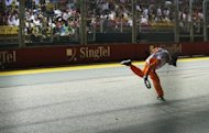 A track marshal runs across the track to remove a piece of debris from a car during Formula One's Singapore Grand Prix. Red Bull's Sebastian Vettel survived an incident-packed Singapore Grand Prix to reignite his world title defence with a thrilling victory on Sunday