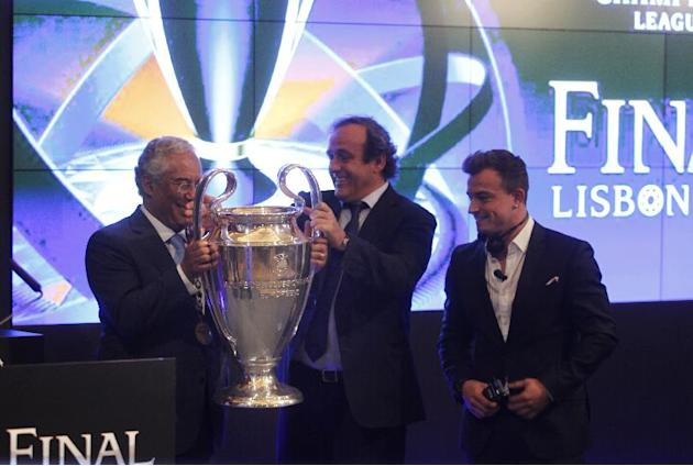 UEFA President Michel Platini, center, gives the Champions League trophy to Lisbon Mayor Antonio Costa,  left, next to German Bayern Munich's soccer player Xherdan Shaquiri during a handover cerem