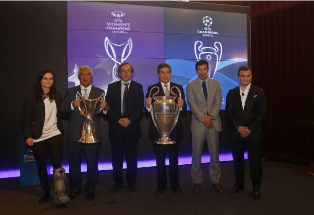 Delegates and soccer players pose for the media with the Champions League trophies during a handover ceremony in Lisbon