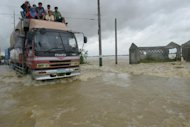 Vehicles drive though flood waters on a road in the northern Philippines on October 12, 2013