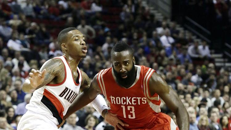 Houston Rockets guard James Harden, right, drives on Portland Trail Blazers guard Damian Lillard during the first half of an NBA basketball game in Portland, Ore., Tuesday, Nov. 5, 2013