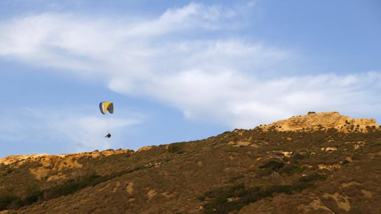 A paraglider soars off a ridge overlooking Ghajn Tuffieha Bay on the northwest coast of Malta