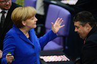 German Chancellor Angela Merkel (L) of the Christian Democratic Union (CDU) talks with Sigmar Gabriel, leader of the social democratic SPD party, at the Bundestag (lower house of parliament) on October 22, 2013 in Berlin