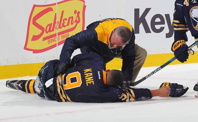 BUFFALO, NY - OCTOBER 13: Evander Kane #9 of the Buffao Sabres is tended to by head athletic trainer Rich Stinziano after crashing into the boards during an NHL game at the KeyBank Center on October 13, 2016 in Buffalo, New York. (Photo by Bill Wippert/NHLI via Getty Images)