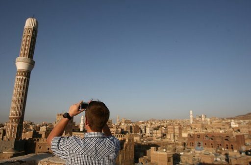 A tourist takes a picture of Sanaa's Old City on January 15, 2010. Gunmen suspected of links to Al-Qaeda kidnapped two Finns and one Austrian in Yemen's capital of Sanaa and drove off with them to an unknown location, security officials told AFP.