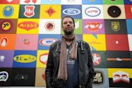 "German artist Konstantin Voit poses for a picture in front of his installation ""Die Malfabrik: Werbeblock"" on display at the exibition ""I love Aldi"" at the Wilhelm Hack Museum in Ludwigshafen am Rhein, western Germany"