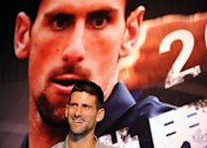Serbian tennis player Novak Djokovic smiles in front of a poster during a news conference in Taipei on September 28. Djokovic aims to reclaim the world number one spot by the end of the year, he said during the promotional tour