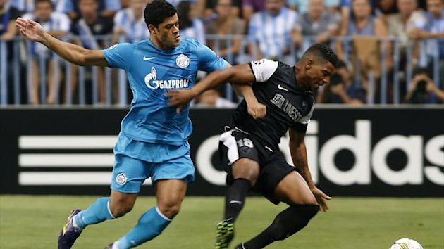 Malaga's Pereira and Zenit St. Petersburg's Hulk battle for the ball battle for the ball