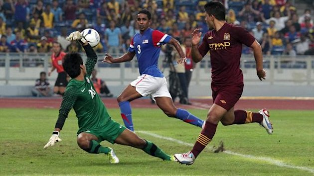 Manchester City striker Sergio Aguero scores against a Malaysia XI at the National Stadium in Kuala Lumpur, which has been deemed unfit for the local Cup final due to a poor playing surface