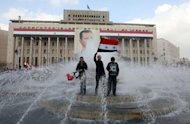 Syrian government supporters wave national flags they stand in a fountain in front of a portrait of President Bashar al-Assad during a pro-regime rally in Damascus on January 26, 2012