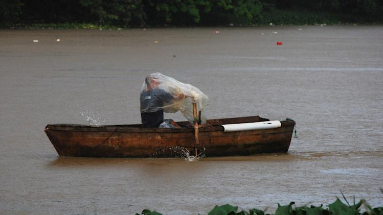A man rowing a boat on the Ozama River protects himself with plastic as rain brought by the outer bands of Tropical Storm Chantal falls in Santo Domingo, Dominican Republic, Tuesday, July 9, 2013. Tropical Storm Chantal threatened to turn into a hurricane while it churned toward the Dominican Republic and Haiti as authorities there and in Puerto Rico warned of possible landslides and heavy flooding. (AP Photo/Ezequiel Abiu Lopez)