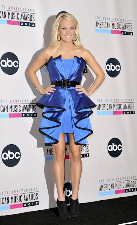 AMAs 2012: Carrie Underwood's second outfit was a bit of a fashion fail. This blue ruffled dress looks somewhere between a dodgy Lady Gaga cast-off and a Quality Street wrapper. We like the shoe boots