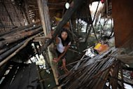 A resident climbs up the collapsed floor of her house in General MacArthur, eastern Samar province, in the central Philippines on September 2. More than 800 homes and businesses were damaged when a 5.6-magnitude earthquake rocked the southern Philippines, officials said