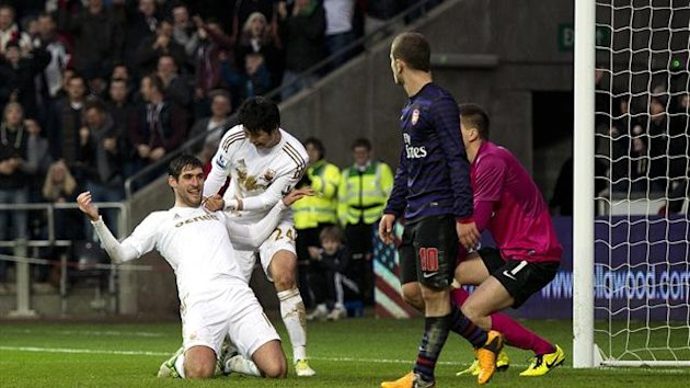 Swansea City's English striker Danny Graham (L) celebrates scoring their second goal to equalise late in the game with teammate Ki Sung-Yueng (2nd L) against Arsenal during the FA Cup third round football match (AFP)