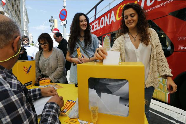 Laia and Laura cast their ballots at a stand of the Catalan National Assembly ANC) during Sant Jordi's day celebrations in Barcelona