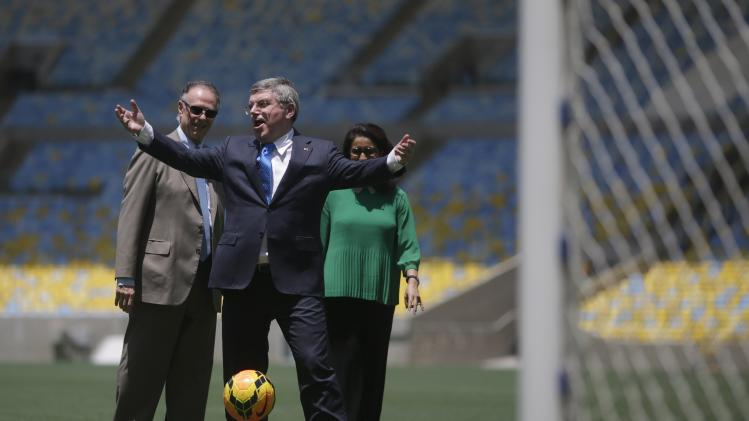 IOC President Thomas Bach gestures as he plays with a ball as President of Brazil's Olympic Committee Arthur Nuzman and IOC Evaluation Commission head Nawal El Moutawakel observe during a visit to Maracana stadium in Rio de Janeiro