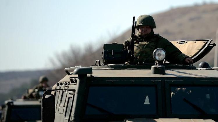 An armed man stands guard with a machine gun on top of an armoured vehicle at a check point on the road from Simferopol to Sevastopol, Ukraine, on March 13, 2014