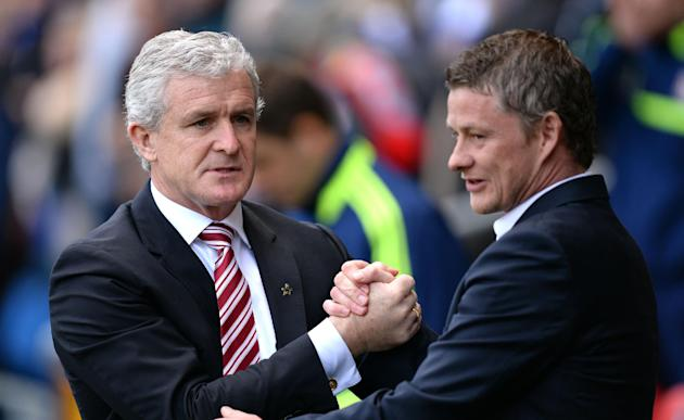 Cardiff City manager Ole Gunnar Solskjaer, right, shakes hands with Stoke City manager Mark Hughes before their English Premier League soccer match at the Cardiff City Stadium, Cardiff, Wales, Saturda