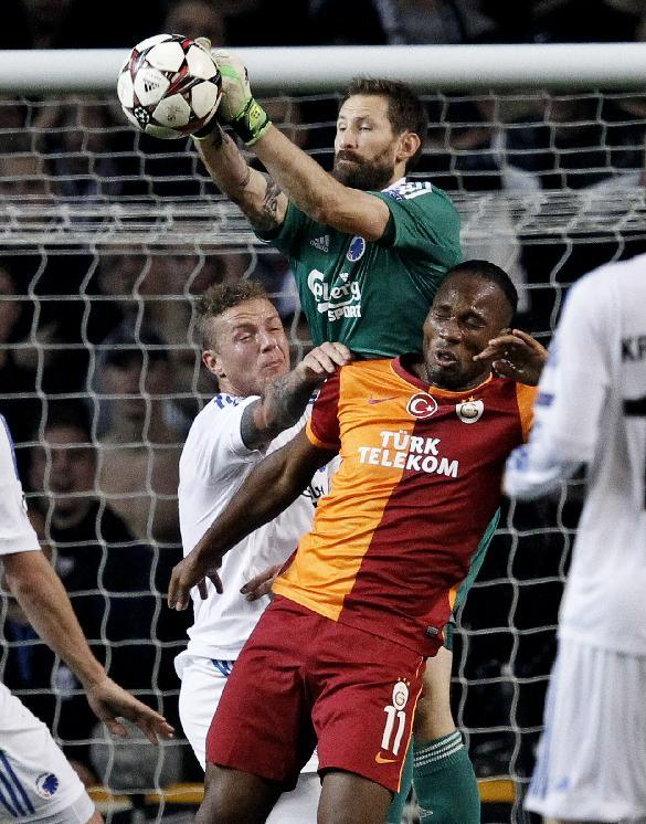Galatasaray's Didier Drogba, right, and FC Copenhagen's goalkeeper Johan Wiland of Sweden, center, compete for the ball during their Champions League Group B soccer match at Parken Stadium, Copenhagen, Denmark, Tuesday Nov. 5, 2013