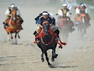 "People in samurai costumes ride horses during a horse racing event at the annual ""Soma Nomaoi"" festival in Minamisoma, Fukushima Prefecture, on July 28. The traditional festival kicked off for the first time since the 2011 quake-tsunami disaster"