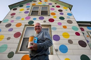 Jim Deitz puts the final touches on his polka dot house. (AP Photo/Grand Forks Herald, Eric Hylden)