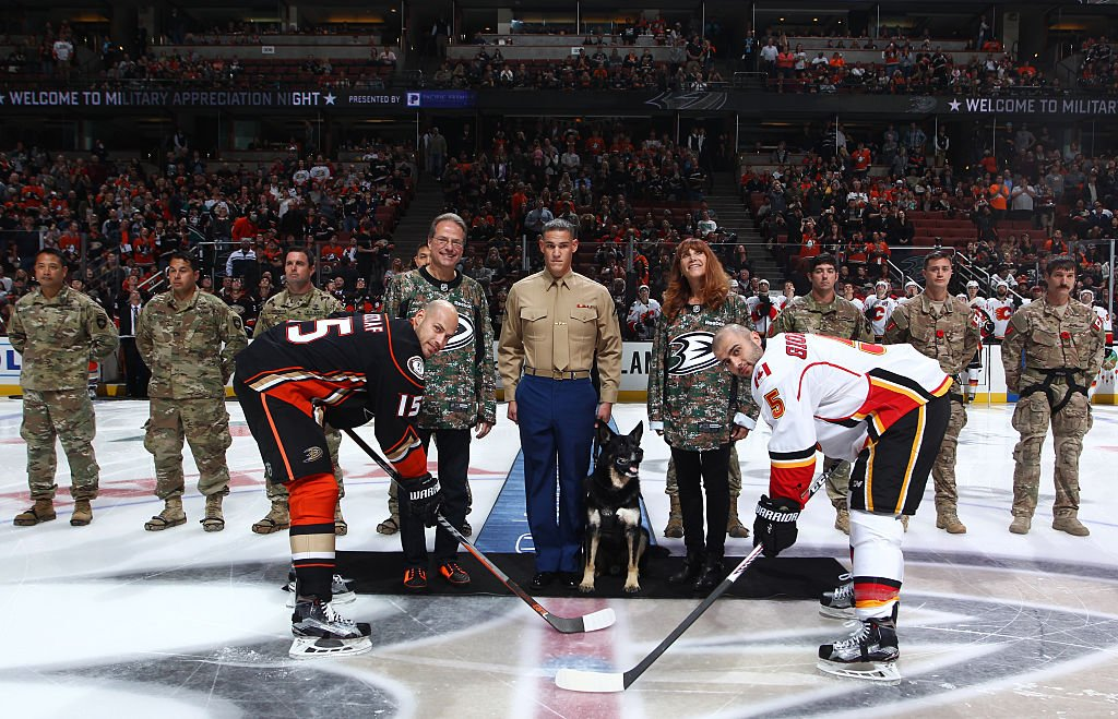 ANAHEIM, CA - NOVEMBER 6: Corporal Nero and Lance Corporal Brandon C. Benningfield, center, are joined by Ryan Kesler #17 of the Anaheim Ducks, Mark Giordano #5 of the Calgary Flames, Ducks owners Henry Samueli, left, and Susan Samueli, and members of the Canadian Special Operations Forces Command, U.S Special Forces Soldiers from Special Operations Detachment North, and the 128th Quartermaster Rigger Support Team for the ceremonial puck drop prior to the game between the Anaheim Ducks and the Calgary Flames on November 6, 2016 at Honda Center in Anaheim, California. (Photo by Debora Robinson/NHLI via Getty Images)