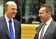 French Finance Minister Pierre Moscovici (L) speaks with his Greek counterpart Yannis Stournaras at the EU Headquarters for a eurogroup meeting on December 13, 2012 in Brussels. France and Germany, seemingly set on divergent political paths, pulled out all the stops Thursday to lay the symbolic foundation stone towards greater eurozone integration.