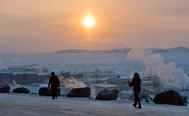 People walk along a path in Iqaluit, Nunavut on Tuesday, December 9, 2014. A long-running study concludes that the well-being of northerners in Canada's Arctic compares poorly with those in many other Arctic regions around the world. THE CANADIAN PRESS/Sean Kilpatrick