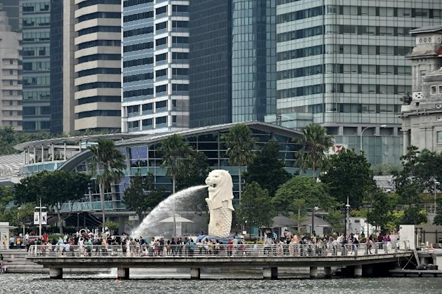 Tourists gather on a jetty around the Merlion next to the financial business district in Singapore on October 31, 2014