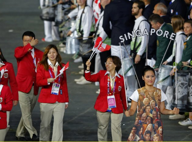 Singapore's athletes wave as they march on the parade during the opening ceremony of the London 2012 Olympic Games at the Olympic Stadium. REUTERS/Mike Blake