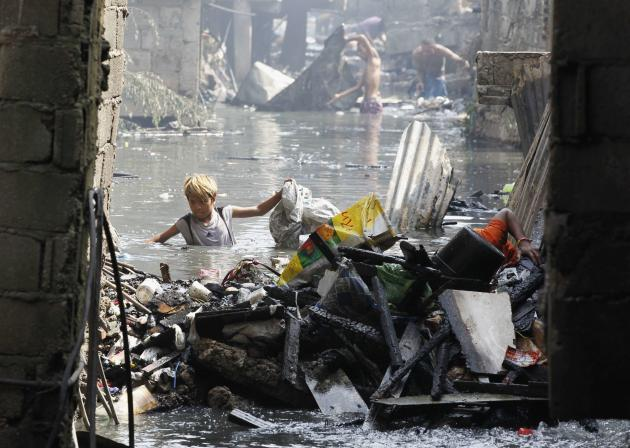 A boy wades through creek while collecting reusable materials after fire razed through residential slum area in Caloocan City, Metro Manila