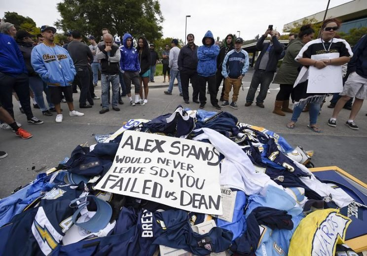 Disappointed fans stand around a pile of Chargers memorabilia in front of the team's old headquarters. (AP)