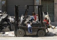 Children play on a forklift in Aleppo September 9, 2013. REUTERS/Muzaffar Salman