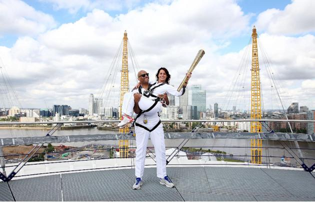 The photo provided by LOCOG shows torchbearers Nadia Comaneci, right, and John Amaechi posing with the Olympic Torch on the viewing platform of the North Greenwich Arena, London, Saturday, July 21, 20