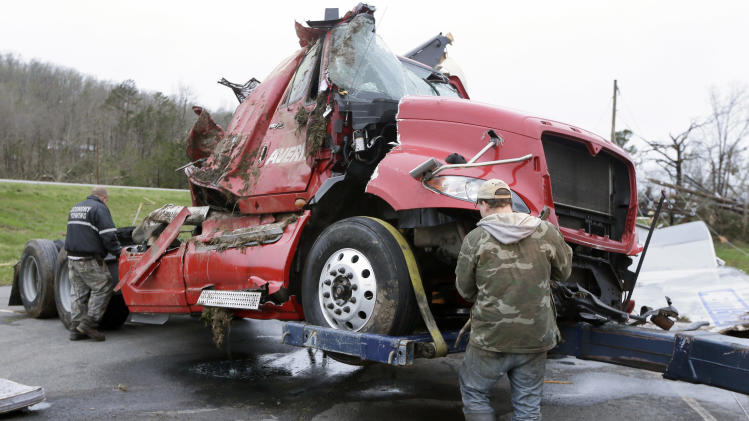 Two men work to remove a truck in Botkinburg, Ark., Thursday, April 11, 2013, that was overturned when a severe storm struck the area late Wednesday. The National Weather Service is surveying areas Thursday to determine whether tornadoes or strong winds caused damage. (AP Photo/Danny Johnston)
