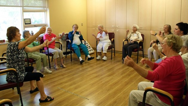A staff member at the Alzheimer Society of Sudbury-Manitoulin leads seniors in a class called Ageless Grace. (CBC Photo)