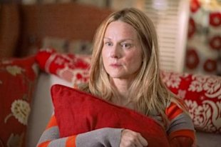 Laura Linney clutches a fancy throw pillow in