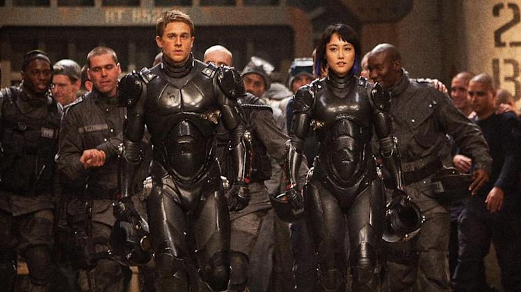 "This publicity photo released by Warner Bros. Pictures shows, front from left, Charlie Hunnam as Raleigh Becket and Rinko Kikuchi as Mako Mori in Warner Bros. Pictures' and Legendary Pictures' sci-fi action adventure, ""Pacific Rim,"" a Warner Bros. Pictures release. (AP Photo/Warner Bros. Pictures, Kerry Hayes)"