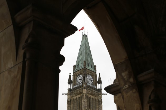The Canadian flag flies at half-mast on the Peace Tower on Parliament Hill in Ottawa October 23, 2014. A gunman attacked Canada's parliament on Wednesday, with gunfire erupting near a room where Prime Minister Stephen Harper was speaking, and a soldier was fatally shot at a nearby war memorial, jolting the Canadian capital. REUTERS/Chris Wattie (CANADA - Tags: POLITICS CRIME LAW MILITARY)