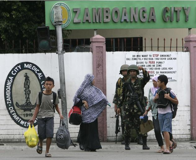 A government soldier directs civilian evacuees near an area where Muslim rebels members of the MNLF is occupying villages in Zamboanga City