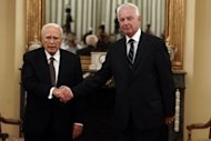 Greek President Carolos Papoulias (L) shakes hands with newly appointed caretaker Prime Minister Panagiotis Pikrammenos (R) in Athens. The senior judge was sworn as caretaker prime minister with the sole task of holding new elections in June after an inconclusive ballot on May 6