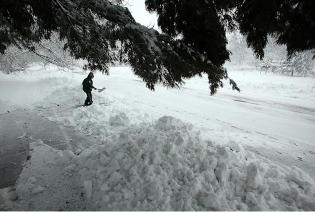 Chris Sauer shovels snow from her driveway during a winter snow storm in Oregon, Wis., Thursday, Dec. 20, 2012.  The first major snowstorm of the season began its slow eastward march across the Midwes