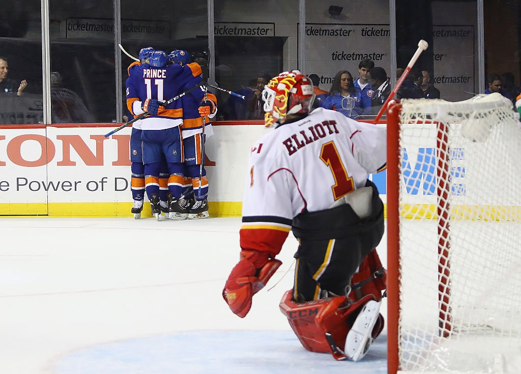 NEW YORK, NY - NOVEMBER 28: (L-R) Thomas Hickey #14 and Shane Prince #11 of the New York Islanders celebrate Hickey's game winning overtime goal against Brian Elliott #1 of the Calgary Flames at the Barclays Center on November 28, 2016 in the Brooklyn borough of New York City. The Islanders defeated the Flames 2-1 in overtime. (Photo by Bruce Bennett/Getty Images)