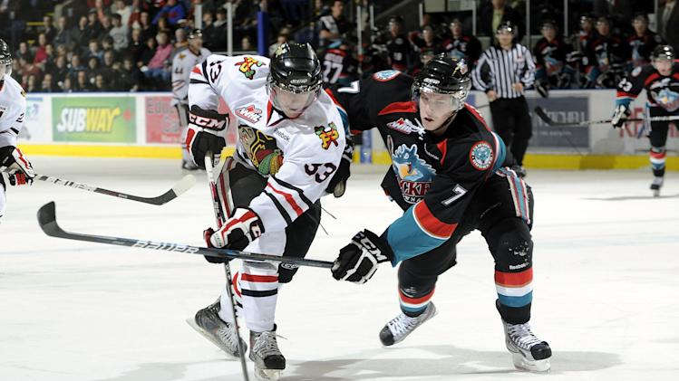 Nic Petan #33 of the Portland Winterhawks is checked by Damon Severson #7 of the Kelowna Rockets
